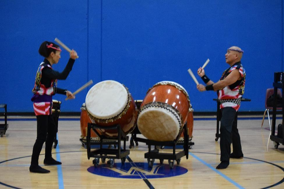 The performers playing the taikos (big drums).