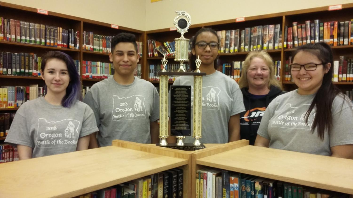 Jasmine Bailey, Israel Sierra, Adrianna Sapp, Teri Morrison (coach) and Savaun Deng pose with their trophy after winning the Battle of the Books regional competition for the second year in a row.